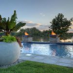 Large cast concrete planter with fire/water features in background.